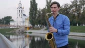 действие : Saxophonist plays the trumpet. City Embankment. man with a whiskered up mustache playing a musical instrument on the streets of the city. saxophone Linton