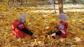 lista : Autumn. Small children in the yellow leaves. Children play in the street with fallen leaves. Autumn grove of birches and maples. Boys throw up fallen leaves of trees in the top. Children sit across from each other on a carpet of yellow leaves and throw le
