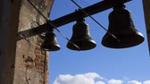 dnes : bells on the background of blue sky with clouds. Bells of various sizes hang in a brick arch at high altitude.