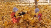 prima infanzia : Autumn. Small children in the yellow leaves. Children play in the street with fallen leaves. Autumn grove of birches and maples. Boys throw up fallen leaves of trees in the top. Children sit across from each other on a carpet of yellow leaves and throw le