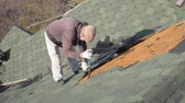 dekarz : Dismantling the soft roof. French green tile. Roofer working on a sloping roof. A man with a beard tears off an old roofing material from a wooden slab with the help of a crowbar. Construction work at height. Wideo