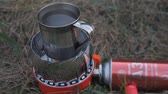 поход : Gas mobile burner stove. Gas cylinder connected to the gas band. metal mug filled with water is heated on a portable tile. GAS