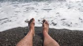 tornozelo : Mens hairy legs in sea surf. Parallel lying bare legs.