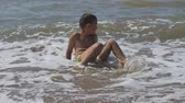 記章 : baby on the beach, in the maritime wave. boy on the golden sand playing in the surf. wave with the head covers the child.
