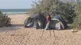 kemping : Tourist camp, tents and a car are in the tourist parking lot. On the tripod of the photographer hanging the swimsuit moving gusts of wind. Stock mozgókép
