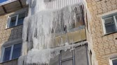 icicle : Winter. Icicles hanging from the roof and balconies of an apartment building Stock Footage