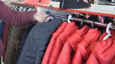 выбор : Clothes hanging neatly on hangers. Female hand chooses outerwear jacket.
