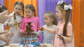 tréfa : Childrens playroom. Children eat chocolate from a chocolate fountain.