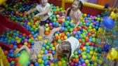 palline colorate : Childrens playroom. Children play in a dry basin filled with plastic colored balls.