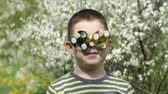 Spinner on the glasses is spinning. Fun on the street. A child on the background of blossoming white flowers of cherry tree. Wideo