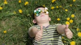 Spinner on the glasses is spinning. Fun on the street. Boy on a background of yellow flowers, dandelions.