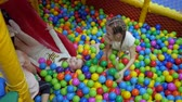 Childrens playroom. Children play in a dry basin filled with plastic colored balls.