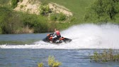 капелька : Jet ski on the river. Splashes fly apart. A man on a water bike splits the water.