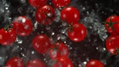 Exploding cherry tomatoes with water on a black background.