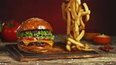 crumble : French fries fall next to cheeseburger, lying on vintage wooden cutting board. Super Slow motion