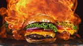 saco : Tasty cheeseburger, lying on vintage wooden cutting board with fire flames in background. Super Slow motion Stock Footage
