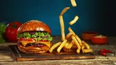 ハンバーガー : French fries fall next to cheeseburger, lying on vintage wooden cutting board. Super Slow motion