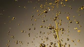Super Slow Motion Shot of Splashing Oil on Golden Background Wideo
