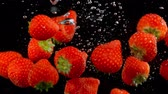 Exploding strawberries with water on a black background.