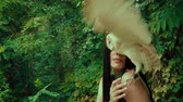 A forest nymph with long dark hair walks with a white owl. A girl in an unusual green dress with a deep neckline and bare legs. Background wild nature