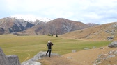 turistler : photographer taking a photo on rock cliff of castle hill view point in road to arthur pass national park south island new zealand important destination to visiting Stok Video