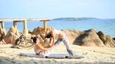 two woman playing yoga pose on sea  beach