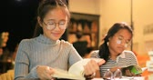 teenagers : asian teenager reading book in school library