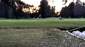 Hitting a Golf Ball with a Driver Golf Club at a Driving Range in the Early Evening Stock Footage