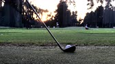 hitting a golf ball off the turf with an iron club at a driving range in the evening