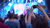 aplauso : European girl takes a photo video shooting panoramic view look of the concert front of the stage phone technology feelings emotions impressions 4k