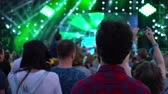 аплодисменты : Footage of a crowd partying at a rock concert young black-haired man guy with curly hair in a plaid shirt looks, animation motion design friendly shot 4k