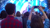 Young couple enjoying the concert, girl shooting memories with her smartphone, technology entertainment Close up of recording video with smartphone during a concert 4k