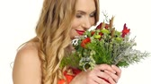 carmesim : Pretty young blonde woman in beautiful red dress smells bouquet of flowers, smiling, isolated on white background, cam moves upward, slow motion Vídeos