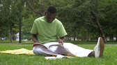 casual : African-American man writes in a notebook at the park.  summer, internet, education, campus and teenage concept - group of students. slow motion