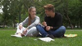 casual : Happy Smiling Couple in love of students Relaxing on Green Grass.Park.Young Couple Lying on Grass Outdoor. slow motion