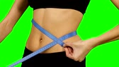 regimen : Woman taking body measurements - isolated over a green , sportswear. details, athletic body, waist