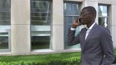 American Businessman talking on cell phone, standing in front of his office. slow motion Stock Footage