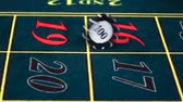 opportunities : Croupier twists chip on green table at casino, front view