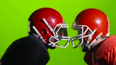 riot control : Two football players face helmets on the field. Green screen. Close up