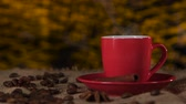 condensed : Cup of coffee with cinnamon and beans scattered on the table. Blurred background