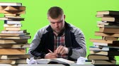 gravado : Man sitting at his desk writes his notes. Green screen