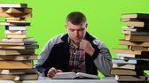 gravado : Man sitting at his desk leafing through a textbook. Green screen Stock Footage