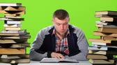 хром : Man sitting at table with books and reading an interesting chapter. Green screen