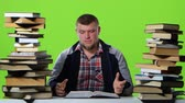 gravado : Man leafing through a textbook, it suffers from headaches. Green screen