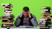 króm : Man leafing through a textbook, it suffers from headaches. Green screen