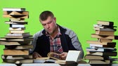 gravado : Man chooses the most interesting book, and writes in a notebook. Green screen