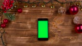 campanário : Phone is on the table, next to the New Years lights. Top view Stock Footage