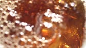 cyst : Cola is poured into a ise glass . White background. Close up. Slow motion