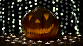 ziyafet : Halloween pumpkin lights inside with flame on a black bokeh background with lighted candles Stok Video