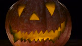 резной : Halloween pumpkin with scary face . Black background. Close up Стоковые видеозаписи